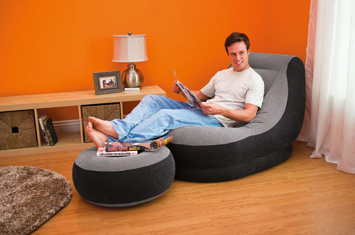 парень отдыхает на надувном кресле с пуфиком